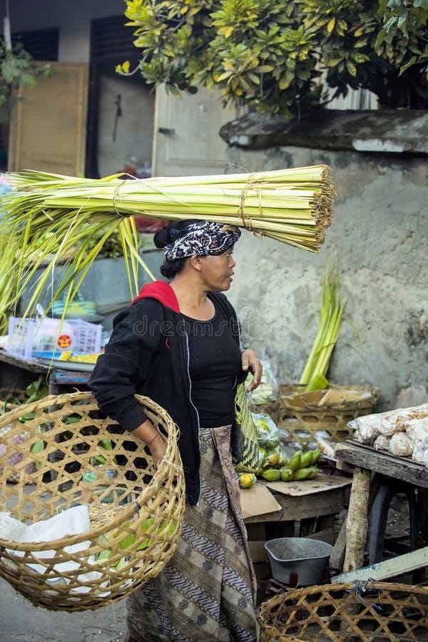 : kvinna med travt på hennes huvud på marknaden, by Toyopakeh, Nusa Penida Juni 17 2015 royaltyfria foton