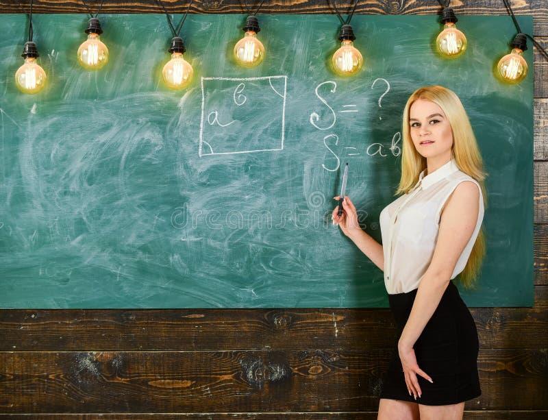 Kvinna med trevliga bakdelar som undervisar matematik Sexigt lärarebegrepp Sexig lärare för dam i kort kjol som förklarar formel arkivbilder