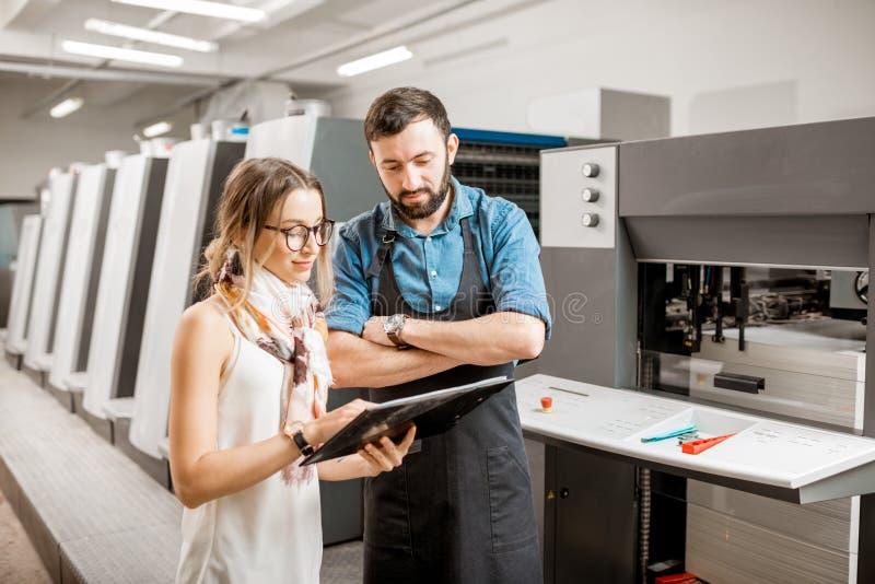 Kvinna med tryckoperatören på printingtillverkningen royaltyfri foto