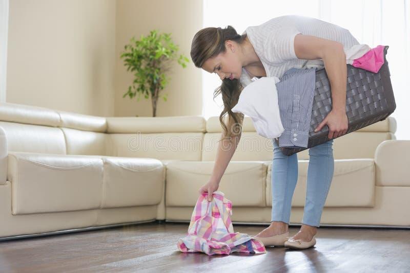 Kvinna med tvättkorgplockningkläder från golv i vardagsrum royaltyfria bilder