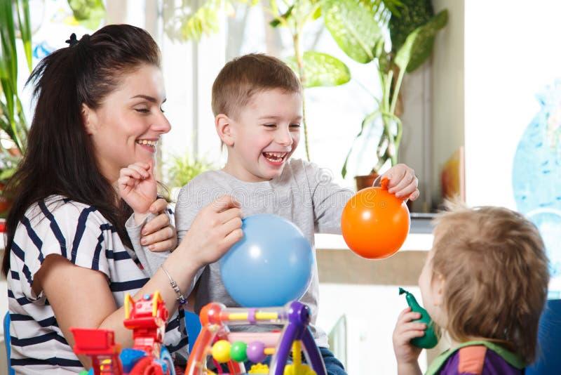 Kvinna med två barn som spelar med ballonger fotografering för bildbyråer