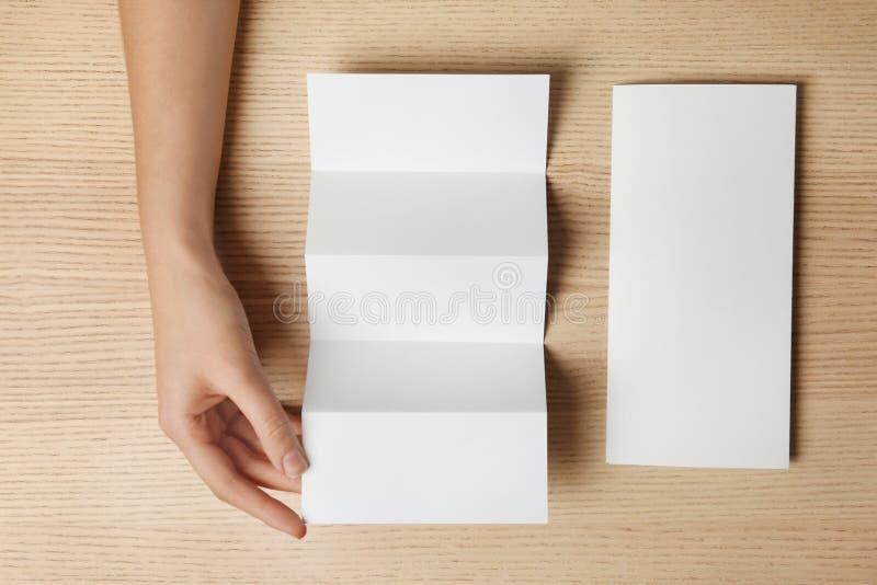 Kvinna med två tomma broschyrer på träbakgrund, bästa sikt royaltyfria foton