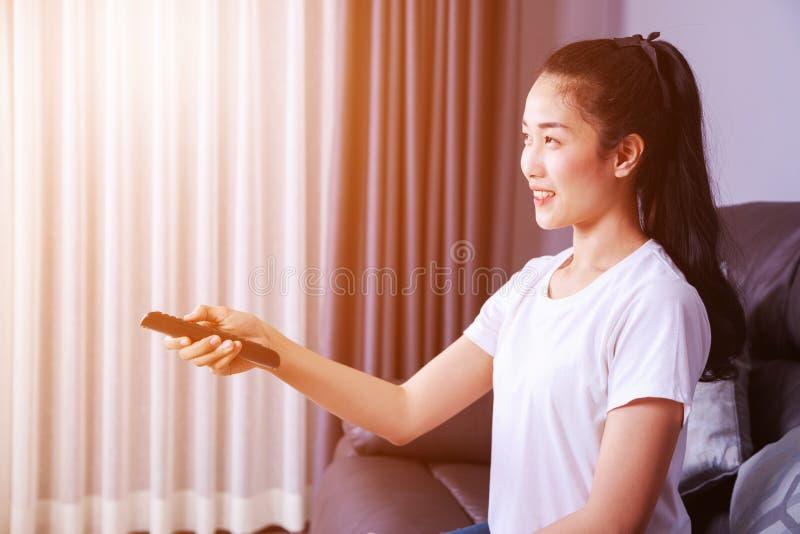 Kvinna med tvfjärrkontroll på soffan hemma arkivbilder