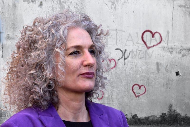 Kvinna med underbart hår framme av en vägg med grafittihjärtor arkivfoton