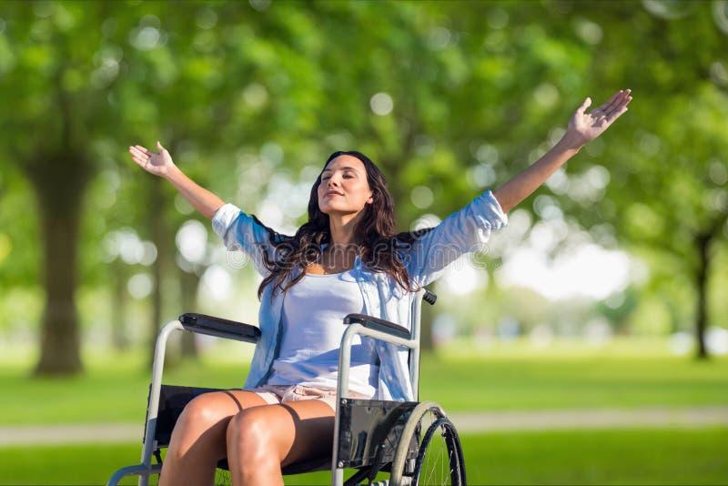 Kvinna med utsträckt sammanträde för armar på rullstolen på fältet royaltyfri fotografi
