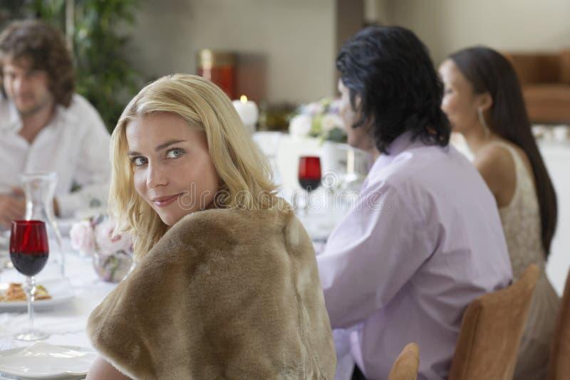 Kvinna med vänner som har matställepartiet hemma arkivbilder
