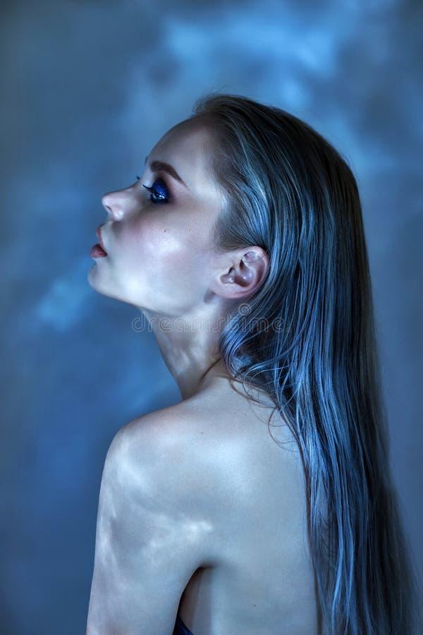 Kvinna med vått hår och ljus makeup som poserar nära vattnet, stående Ilsken blick från vattnet på flickaframsidan, skönhetsmedel royaltyfri fotografi