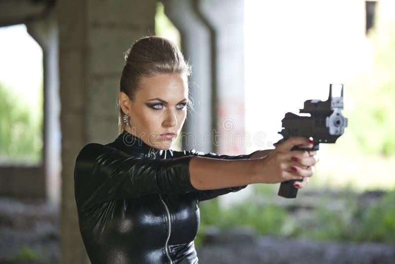Kvinna med vapnet i läderdräkt royaltyfri bild