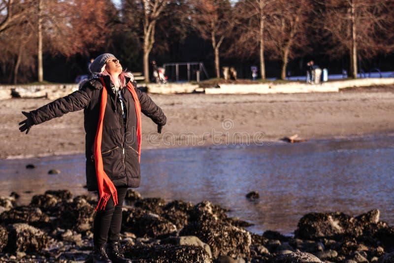 Kvinna med vinterkläder på stranden Halsduk, lag och lock royaltyfri foto