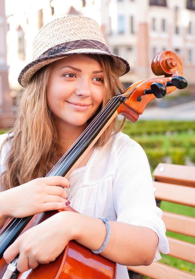 Kvinna med violoncellen på bänken royaltyfri foto