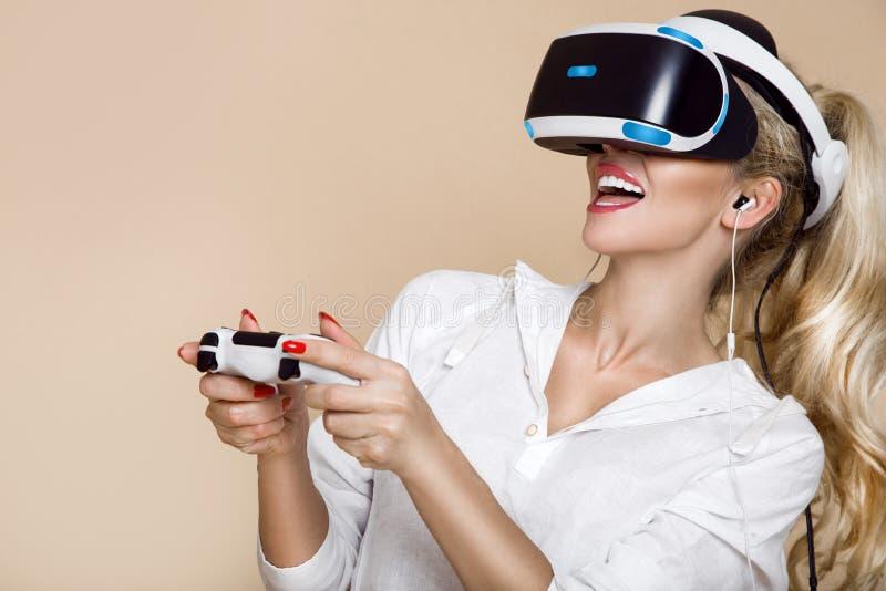 Kvinna med VR-exponeringsglas av virtuell verklighet Ung flicka i faktisk ökad verklighethjälm VR-hörlurar med mikrofon arkivfoto