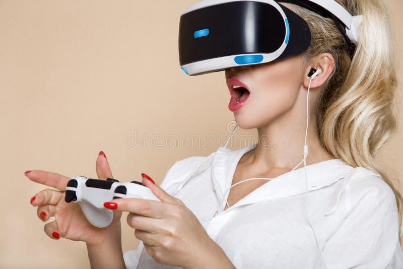 Kvinna med VR-exponeringsglas av virtuell verklighet Ung flicka i faktisk ökad verklighethjälm VR-hörlurar med mikrofon fotografering för bildbyråer