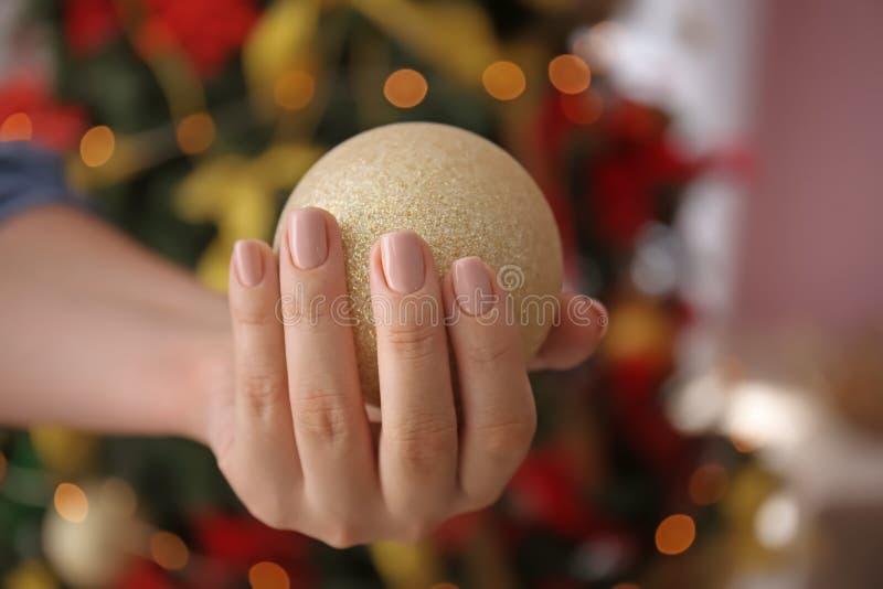 Kvinna med yrkesmässig manikyr som rymmer julbollen, closeup royaltyfri bild