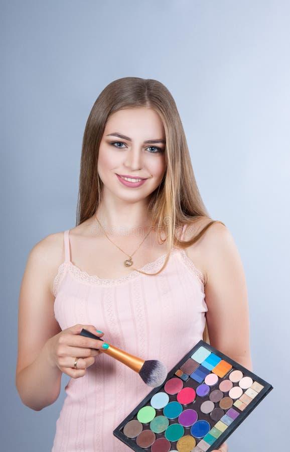 Kvinna med yrkesmässiga Makeup för sminkkonstnär satser royaltyfri bild