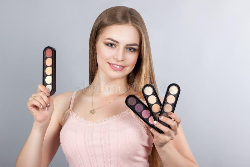 Kvinna med yrkesmässiga Makeup för sminkkonstnär satser arkivfoto
