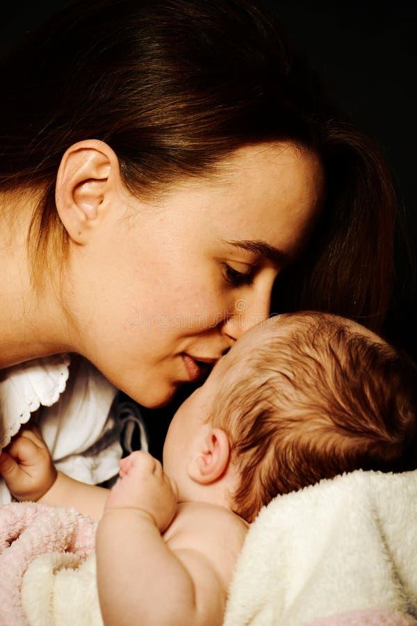 Kvinna moder som ler till barnet arkivbild