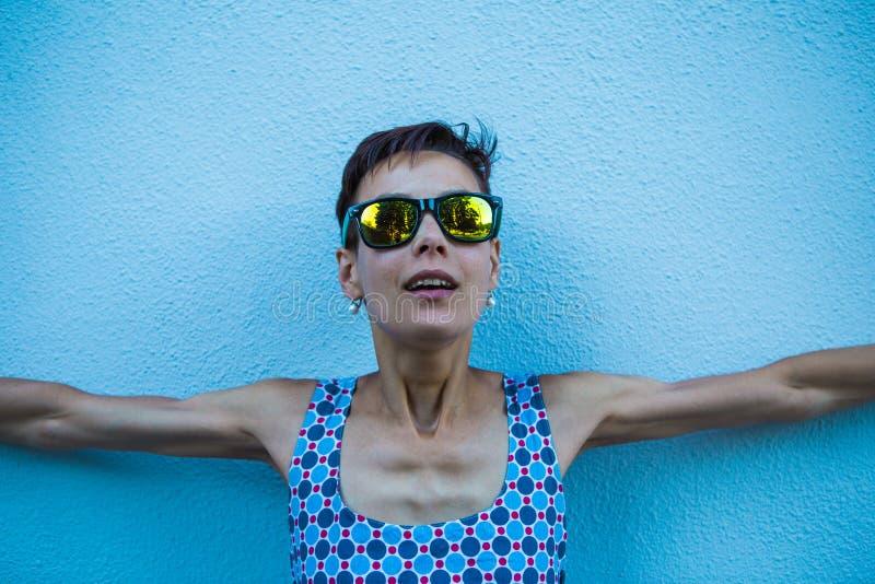 Kvinna mot en blå vägg royaltyfria bilder