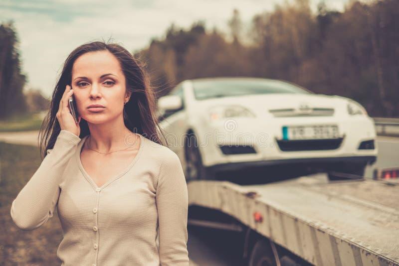 Kvinna nära bärgningsbilen som upp väljer bilen arkivfoton