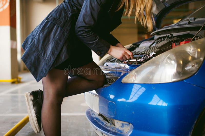 Kvinna nära huven för bil` s den unga blondinen i dold parkering av köpcentret, ställningar nära bilen med hättan för motorrummet royaltyfri bild