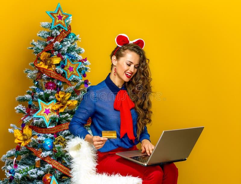 Kvinna nära julgranen som gör online-köp på en bärbar dator royaltyfria foton