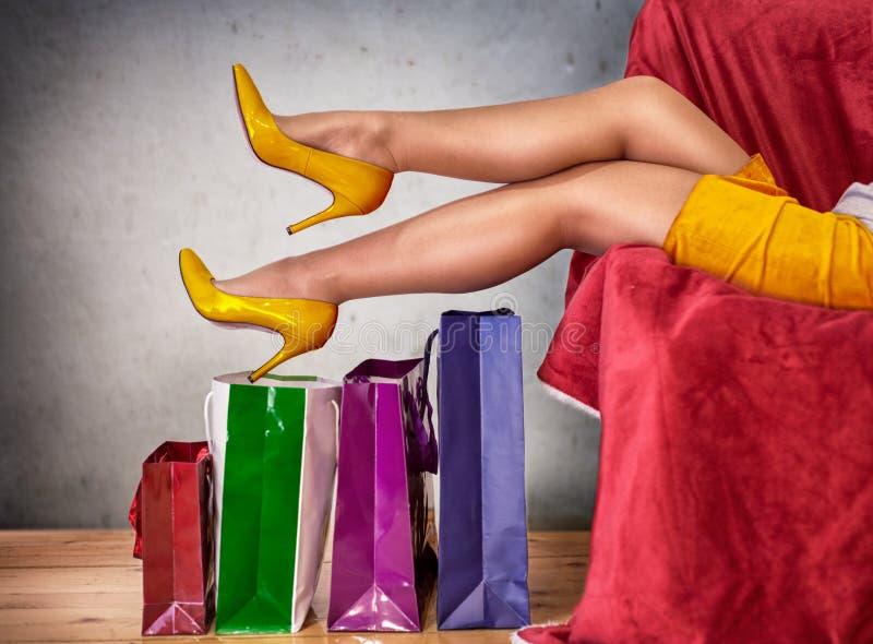 Kvinna når att ha shoppat dag som vilar trötta ben royaltyfri foto
