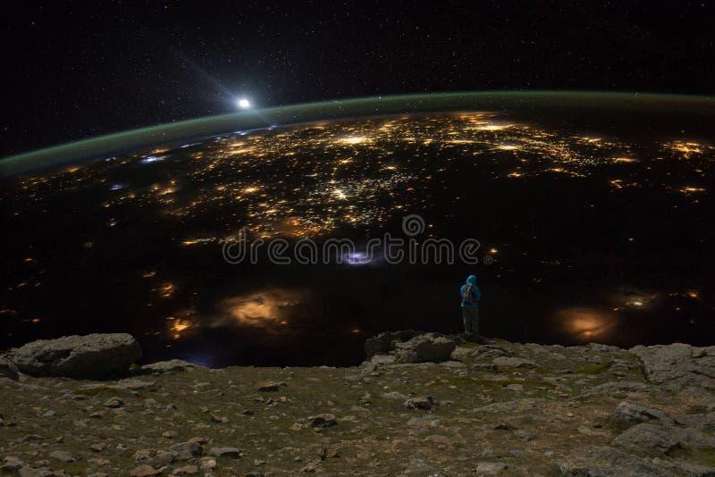 Kvinna observera jorden från en imaginär klippa under natten arkivbild