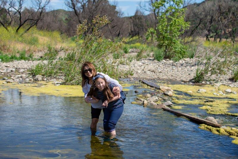 Kvinna och anseende- och skrattatother för dotter, medan spela i en ström eller en flod royaltyfri fotografi