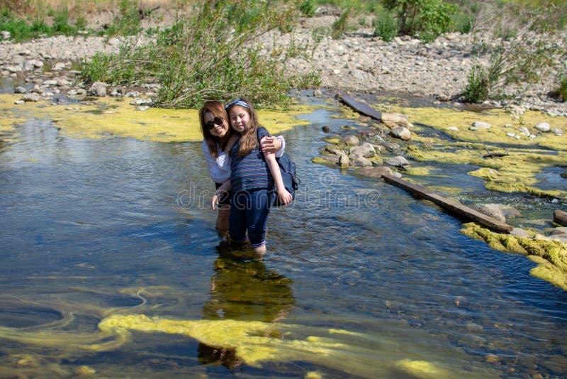 Kvinna och anseende- och skrattatother f?r dotter, medan spela i en str?m eller en flod royaltyfri foto