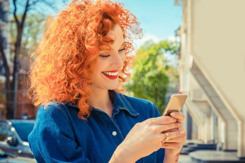 Kvinna och att le och att se hennes smsa för mobiltelefon som läser smsmeddelandet arkivbilder