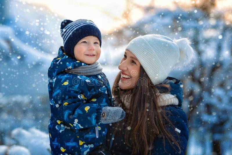 Kvinna och barn i vinter i natur lycklig stående för familj arkivbild