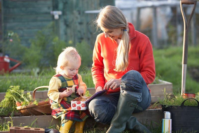Kvinna och barn med picknicken på odlingslott arkivfoto