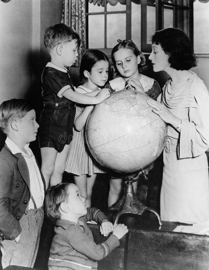 Kvinna och barn som ser jordklotet (alla visade personer inte är längre uppehälle, och inget gods finns Leverantörgarantier som t royaltyfria foton