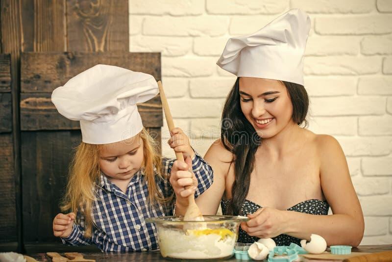Kvinna- och barnpojke i kockhattar med skeden royaltyfria bilder