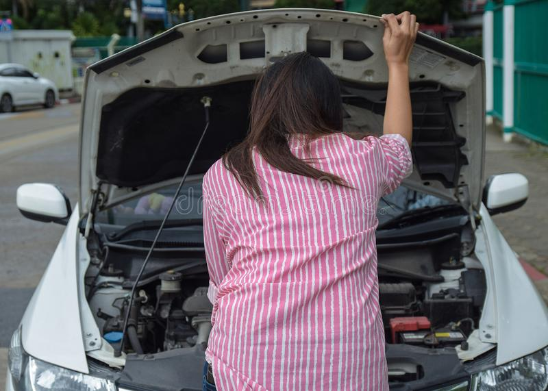 Kvinna och brutet ner bilen på vägen som kontrollerar problem i motor Olycka och sammanbrott med auto begrepp arkivbilder