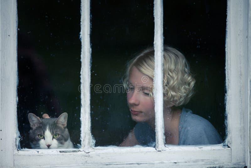Kvinna och Cat Looking på det regniga vädret vid fönstret royaltyfri foto
