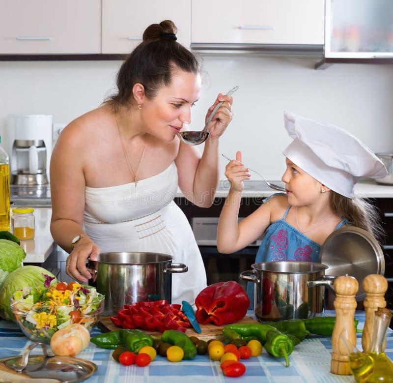 Kvinna och dotter som förbereder sund buljong royaltyfria bilder