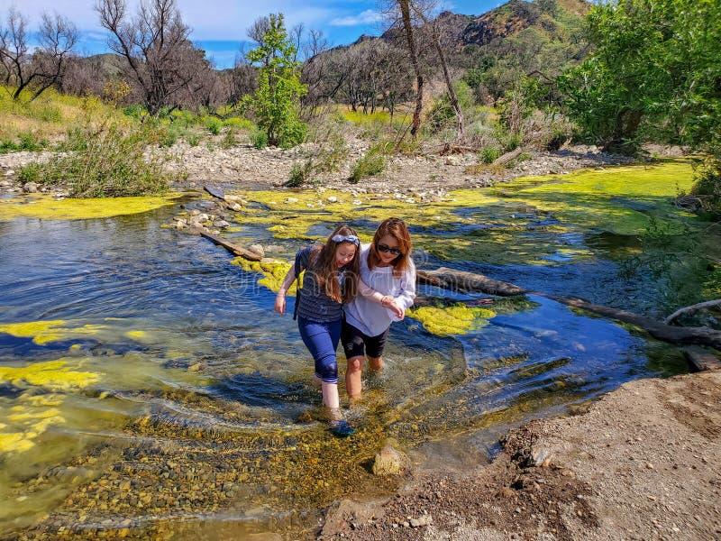 Kvinna och dotter som f?rsiktigt korsar i en str?m eller en flod fotografering för bildbyråer