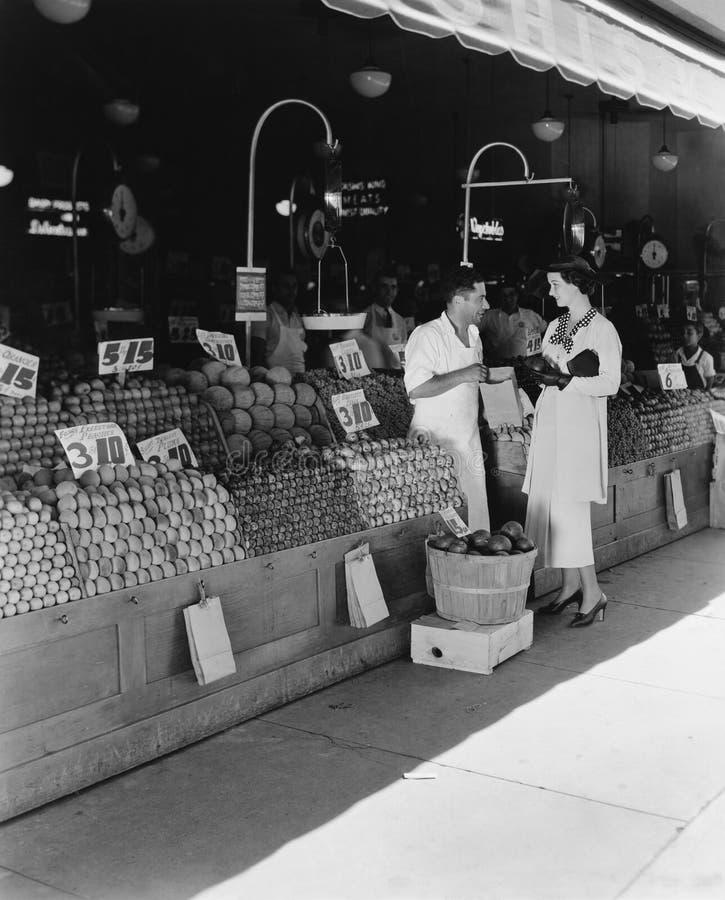 Kvinna och försäljare på marknaden för öppen luft (alla visade personer inte är längre uppehälle, och inget gods finns Leverantör arkivfoto