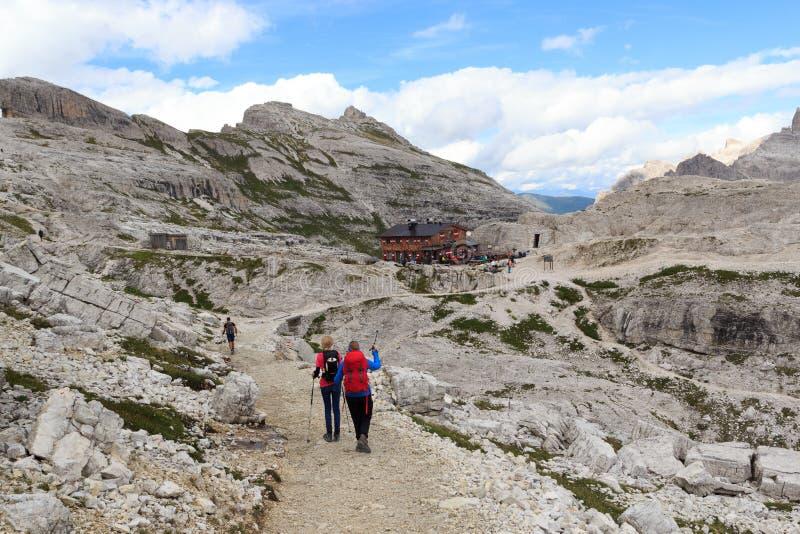 Kvinna och flicka som fotvandrar in mot den alpina kojan Bullelejochhutte i Sexten Dolomites, södra Tyrol arkivbilder
