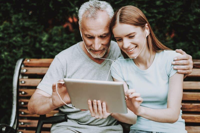 Kvinna och gamal man Sitt på bänk och håll ögonen på lek royaltyfri fotografi