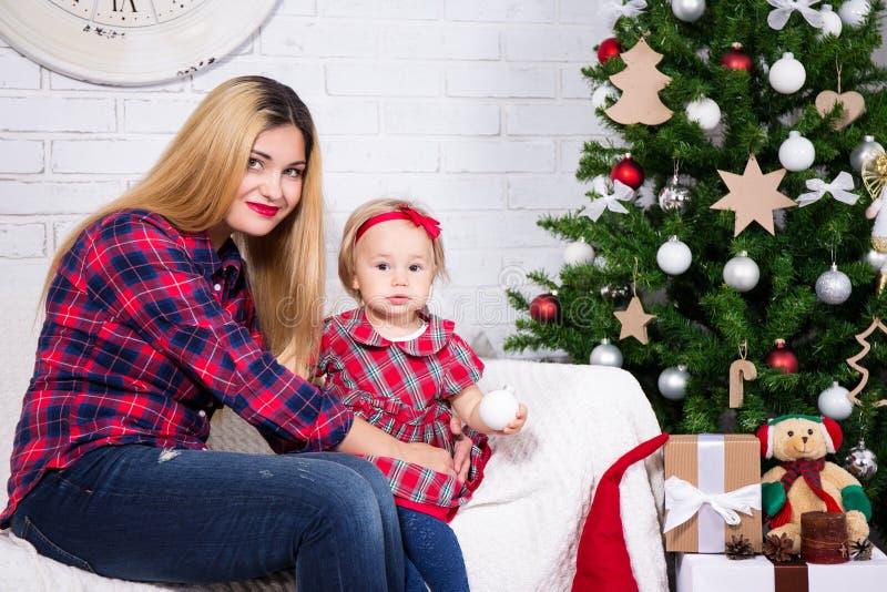 Kvinna och hennes dottersammanträde i dekorerad vardagsrum med Chr royaltyfri foto