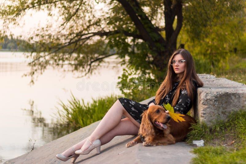 Kvinna och hund som går i parkera Sunda livsstil- och husdjurbegrepp arkivfoto