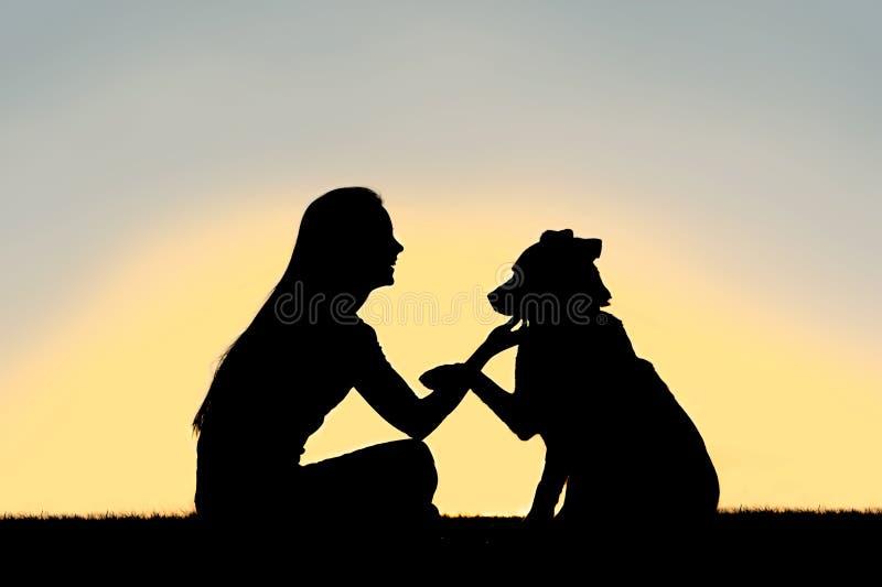 Kvinna och hund som skakar handsolnedgångkonturn fotografering för bildbyråer