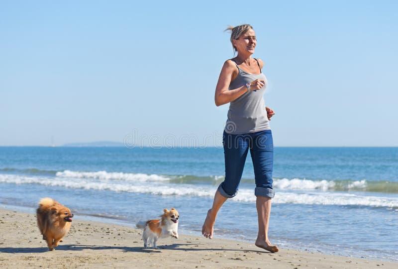 Kvinna och hundkapplöpning på stranden royaltyfri foto