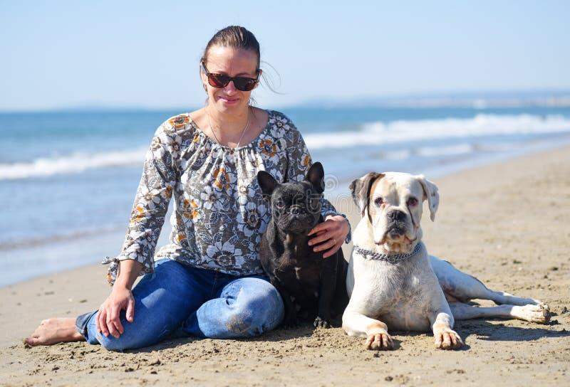 Kvinna och hundkapplöpning på stranden arkivbild