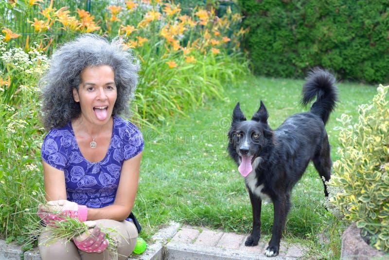 Kvinna- och hundvisning deras tonges arkivbild