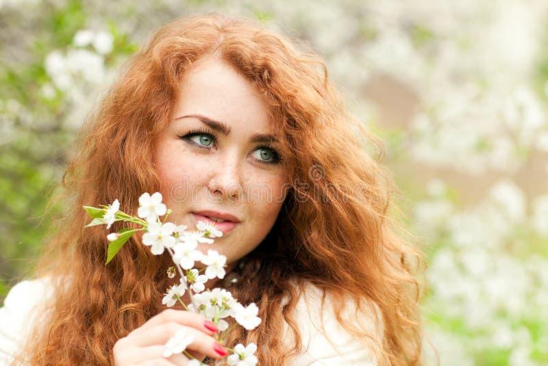 Kvinna och körsbärsröda blomningar royaltyfria bilder