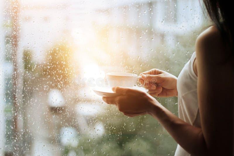 Kvinna- och kaffekopp i händer som ser till och med det glass fönstret royaltyfria bilder