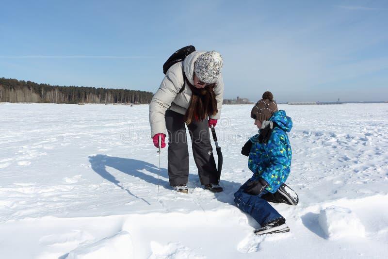Kvinna och lite pojke som sågar ett snökvarter för att bygga en igloo, Novosibirsk, Ryssland arkivfoton