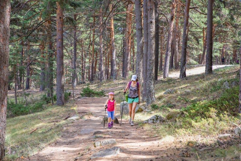 Kvinna och liten flicka som nära fotvandrar på en bana i skog till Madrid royaltyfri fotografi